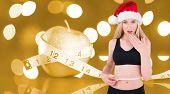 Fit festive young blonde measuring her waist against orange vignette