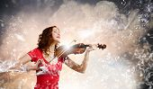 Young pretty woman in red dress playing violin