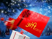 Composite image of red gift card against cute christmas village with tree