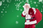 Santa asking for quiet with bag against green