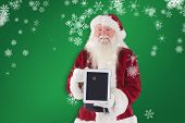 Santa presents a tablet PC against green