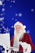 Santa pays with credit card on a laptop against blue