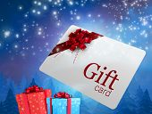 Flying gift card and presents against snow falling on fir tree forest