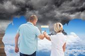 Composite image of happy older couple painting the sky from dark to light