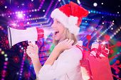 Festive blonde holding megaphone and bags against digitally generated star laser background