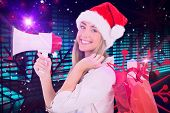Festive blonde holding megaphone and bags against digitally generated disco light design