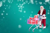 Santa pushes a shopping cart with presents against green snowflake background