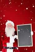 Santa claus showing blackboard against red snowflake background