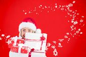 Festive blonde holding pile of gifts against red background