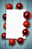 Red christmas baubles surrounding white page against painted blue wooden planks