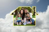 Happy family sitting in the garden against bright blue sky with clouds