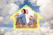 Couple sitting on the floor against blue sky with white clouds