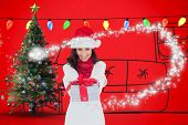 Festive brunette in santa hat giving gift against red background