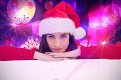 Pretty brunette in santa hat smiling at camera against digitally generated cool nightlife design
