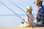 Father and daughter fishing on the pier