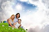 Happy family of mother father and daughter sitting on grass