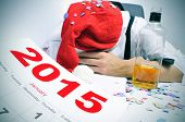 a man with a santa hat and covered with confetti sleeping in his desk after a new years party