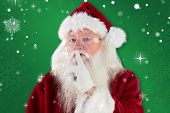Santa asking for quiet to camera against green snowflake background