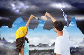 Composite image of happy young couple painting the sky from dark to light