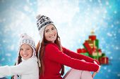 Mother and daughter against blurred christmas background
