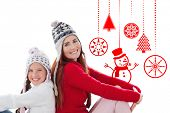 Mother and daughter against hanging red christmas decorations
