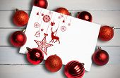 Hanging red christmas decorations against painted blue wooden planks