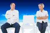 Upset couple not talking to each other after fight against bright blue sky over clouds