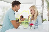 Man proposing marriage to his shocked blonde girlfriend against house outline