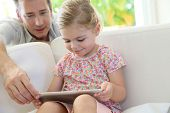 Little girl using tablet with care of her dad