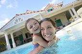 Mother and daughter playing together in pool