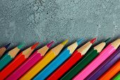 Colorful pencils on texture wooden background