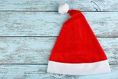 Santa red hat on color wooden background