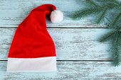 Santa red hat with fir-tree branch on color wooden background