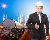 Young Engineering Man With Safety Helmet Standing Against Beautiful Lighting Of Oil Refinery Plant I