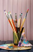 Paint brushes with paints and palette on wooden background