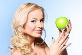 Portrait of a beautiful young woman eating green apple. Healthy nutrition, diet.