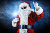 Modern Santa Claus in sunglasses over dark background. Christmas.