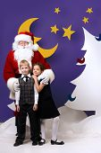 Santa Claus standing with happy children in a cartoon fairy snowy forest. Full length portrait.