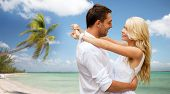 summer holidays, people, love, travel and dating concept - happy couple hugging over tropical beach background
