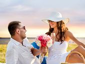 love, dating, people and holidays concept - smiling couple drinking champagne on picnic over seaside sunset background