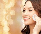 beauty, people and health concept - beautiful smiling woman cleaning face skin with cotton pad over beige lights background