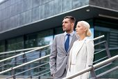 business, partnership, success and people concept - serious businessman and businesswoman standing over office building