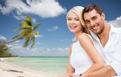 summer holiday, vacation, dating and tourism concept - happy couple having fun and hugging over beach background