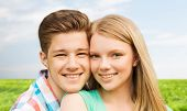 holidays, vacation, love and people concept - smiling teenage couple hugging over blue sky and grass background