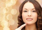 beauty, people and health concept - beautiful young woman pointing finger to her chin over beige lights background