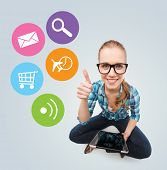 communication, technology, internet and people concept - smiling teenage girl in eyeglasses sitting on floor and holding tablet pc computer over gray background with colorful icons