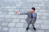 business, development and people and concept - young smiling businessman pointing finger outdoors from top