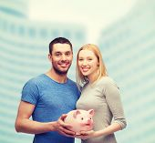 finance, money and family concept - smiling couple holding big piggy bank