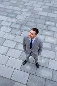 business, development and people and concept - young smiling businessman outdoors from top