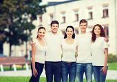 advertising, friendship, education, scool and people concept - group of smiling teenagers in white blank t-shirts over campus background